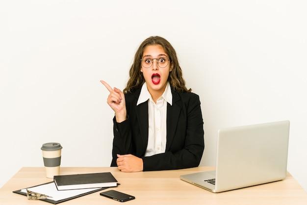 Junge kaukasische geschäftsfrau, die auf ihrem desktop arbeitet, zeigt lokal zur seite