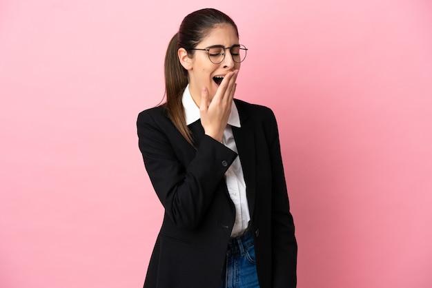 Junge kaukasische geschäftsfrau, die auf rosafarbenem hintergrund isoliert ist, gähnt und den weit geöffneten mund mit der hand bedeckt