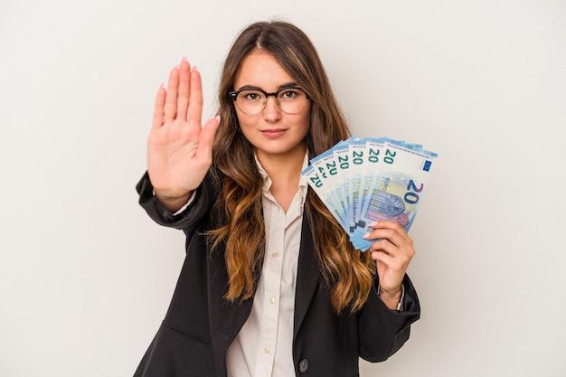 Junge kaukasische geschäftsfrau, die banknoten auf weißem hintergrund hält, die mit ausgestreckter hand stehen, die stoppschild zeigt und sie verhindert.