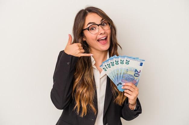 Junge kaukasische geschäftsfrau, die banknoten lokalisiert auf weißem hintergrund hält, der eine handyanrufgeste mit den fingern zeigt.