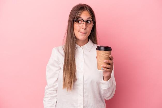 Junge kaukasische geschäftsfrau, die ein mitnehmen einzeln auf rosafarbenem hintergrund hält, verwirrt, fühlt sich zweifelhaft und unsicher.