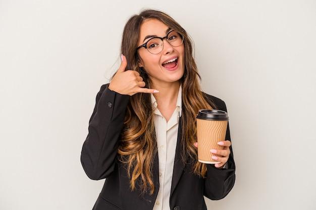 Junge kaukasische geschäftsfrau, die einen kaffee zum mitnehmen lokalisiert auf weißem hintergrund hält, der eine handyanrufgeste mit den fingern zeigt.