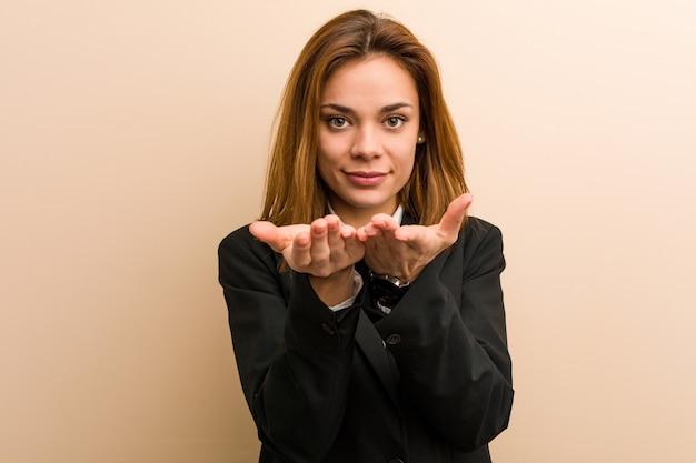 Junge kaukasische geschäftsfrau, die etwas mit den palmen, kamera anbietend hält.