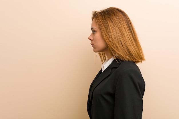 Junge kaukasische geschäftsfrau, die nach links, seitlich haltung anstarrt.