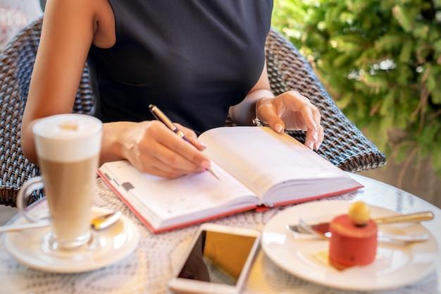 Junge kaukasische geschäftsfrau im schwarzen kleid schreibt im notizbuch, das am tisch im café sitzt