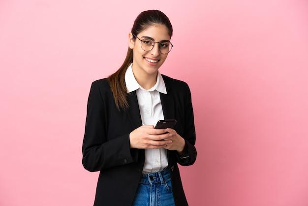 Junge kaukasische geschäftsfrau isoliert auf rosa hintergrund, die eine nachricht mit dem handy sendet