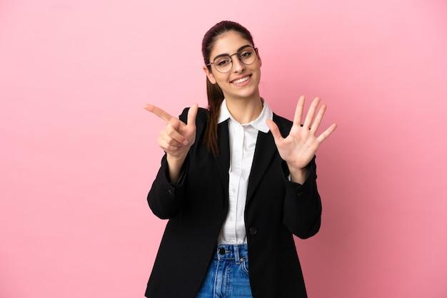 Junge kaukasische geschäftsfrau isoliert auf rosa hintergrund, die mit den fingern sieben zählt