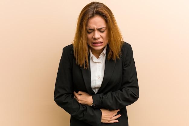 Junge kaukasische geschäftsfrau krank, unter magenschmerzen leidend, schmerzhaftes krankheitskonzept.