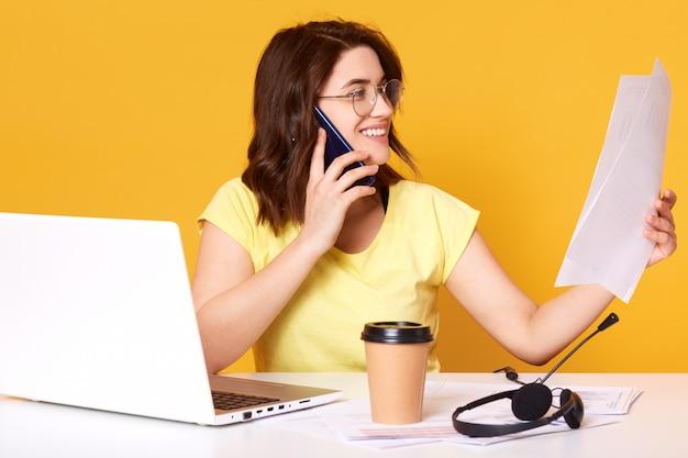 Junge kaukasische geschäftsfrau mit dunklen haaren, die am tisch sitzen und papiere halten, während sie mit ihrem klienten sprechen