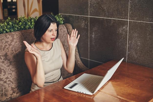 Junge kaukasische geschäftsfrau mit laptop. frau im café