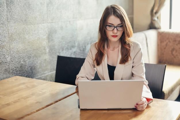 Junge kaukasische geschäftsfrau mit laptop. frau in gläsern in einem café