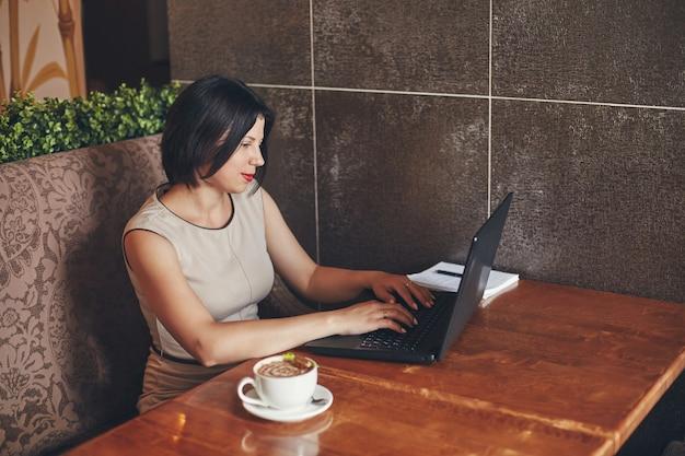 Junge kaukasische geschäftsfrau mit laptop und notizbuch. frau im café