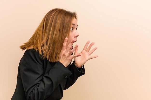 Junge kaukasische geschäftsfrau schreit laut, hält augen geöffnet und hände angespannt.