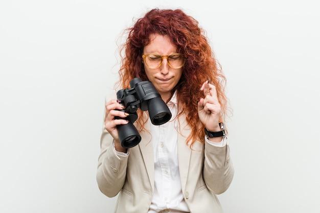 Junge kaukasische geschäftsrotschopffrau, die ein fernglas hält, das finger kreuzt, um glück zu haben