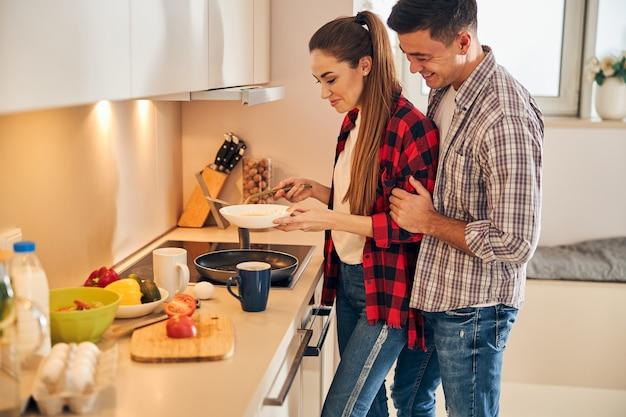 Junge kaukasische hausfrau, die frühstück für zwei zubereitet