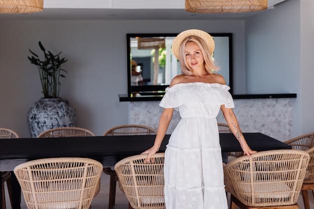 Junge kaukasische hübsche blonde haarfrau in der außenküche an der villa weiblich mit leichtem make-up im weißen sommerkleid und im strohhut im urlaub