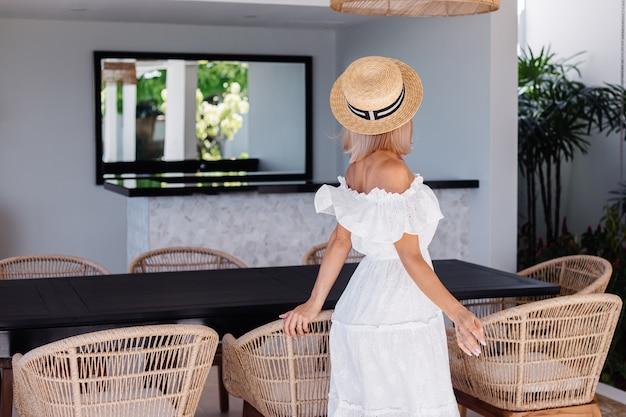 Junge kaukasische hübsche blonde haarfrau in der außenküche an der villa