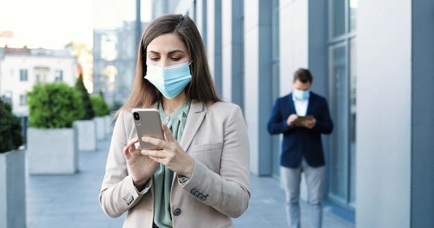 Junge kaukasische hübsche geschäftsfrau in der medizinischen maske, die an der straße am geschäftszentrum und an der sms auf smartphone steht. schöne frau, die auf handy tippt und scrollt. mann auf hintergrund.