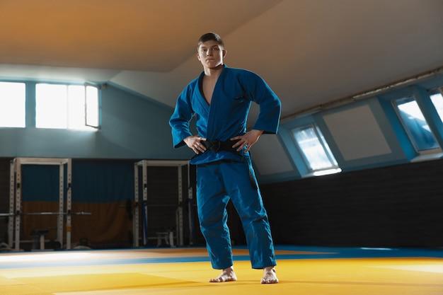Junge kaukasische judokämpferin im blauen kimono mit schwarzem gürtel, die selbstbewusst im fitnessstudio posiert, stark und gesund