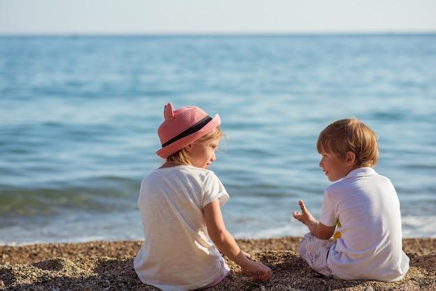 Junge kaukasische kinder am ozeanufer an einem sonnigen sommertag