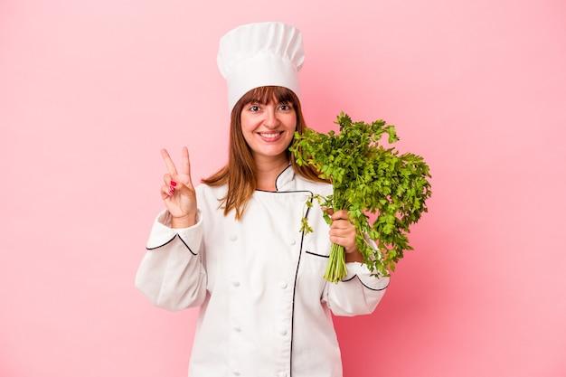 Junge kaukasische kochfrau, die petersilie einzeln auf rosa hintergrund hält und nummer zwei mit den fingern zeigt.