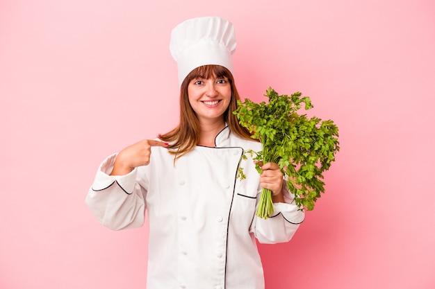 Junge kaukasische kochfrau, die petersilie einzeln auf rosafarbenem hintergrund hält, die mit der hand auf einen hemdkopierraum zeigt, stolz und selbstbewusst
