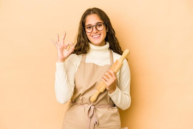 Junge kaukasische kochfrau isolierte fröhliche und selbstbewusste zeigen ok geste.
