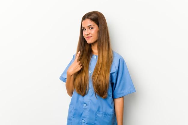 Junge kaukasische krankenschwesterfrau, die mit dem finger auf sie zeigt, als ob die einladung näher kommt.