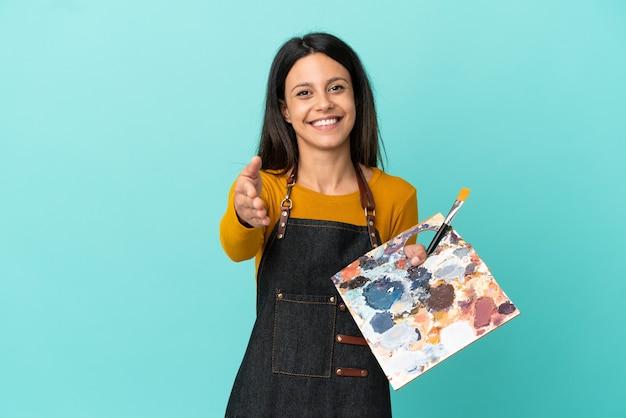 Junge kaukasische künstlerin, die eine auf blauem hintergrund isolierte palette hält, die hände schüttelt, um ein gutes geschäft abzuschließen?