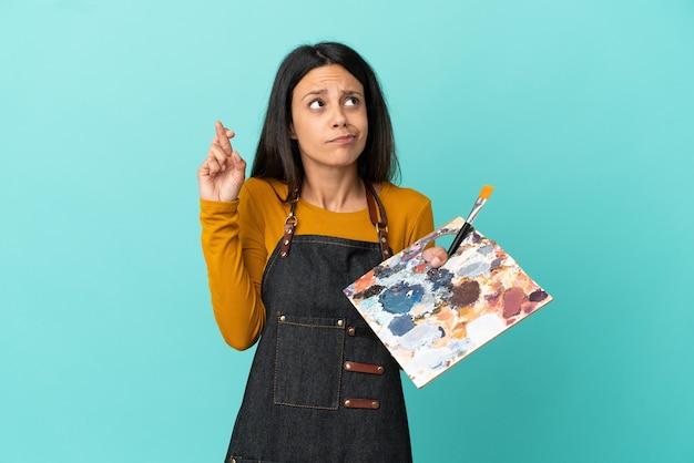 Junge kaukasische künstlerin, die eine palette auf blauem hintergrund mit gekreuzten fingern hält und das beste wünscht