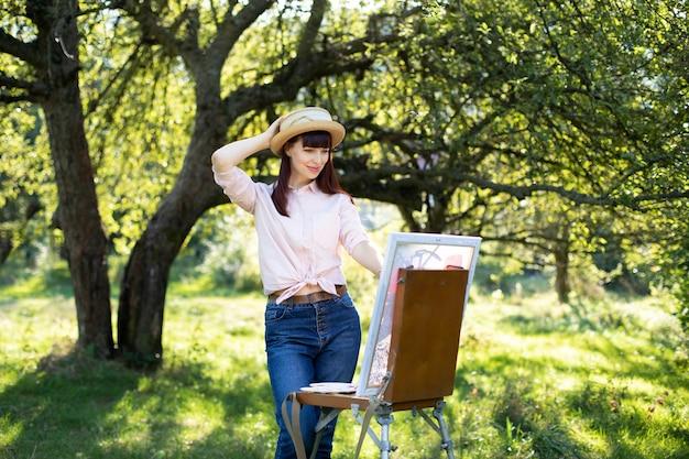 Junge kaukasische künstlerin, trägt jeans, leichtes hemd und strohhut und malt ein bild auf einer staffelei im sonnigen sommerpark.
