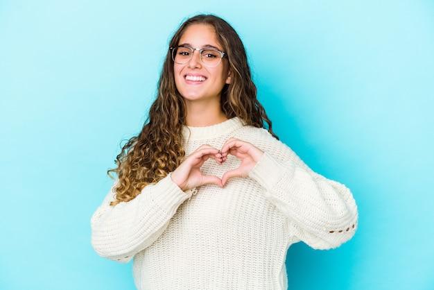 Junge kaukasische lockige haarfrau lokalisiert lächelnd und zeigt eine herzform mit händen.