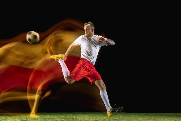 Junge kaukasische männliche fußball- oder fußballspieler in sportbekleidung und stiefeln, die bei gemischtem licht auf dunkler wand den ball für das tor treten. konzept des gesunden lebensstils, des profisports, des hobbys.