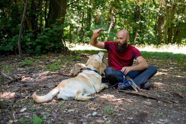 Junge kaukasische männliche touristen erkunden schöne orte mit seinem labrador retriever places
