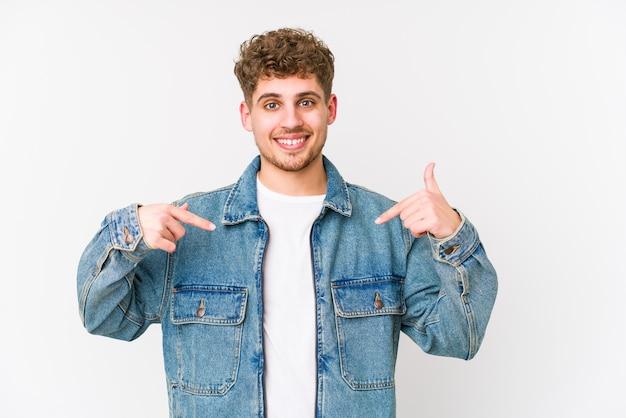 Junge kaukasische mann des blonden lockigen haares isolierte person, die von hand auf einen hemdkopierraum zeigt, stolz und zuversichtlich