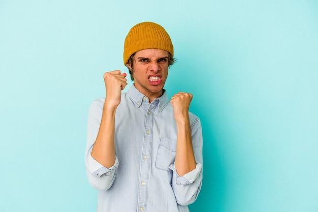 Junge kaukasische mann mit make-up auf blauem hintergrund isoliert verärgert schreiend mit angespannten händen.