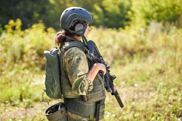 Junge kaukasische militärfrau hält eine waffe in der hand in der natur