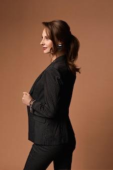 Junge kaukasische modelfrau mit natürlichem make-up, die formelle und trendige bürokleidung über beige trägt ...