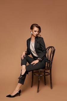 Junge kaukasische modellfrau in einer grauen anzugbluse und schwarzen schuhen, die auf dem stuhl an der beigefarbenen wand sitzen, isoliert mit kopierraum