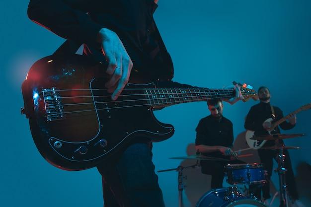 Junge kaukasische musiker, band, die im neonlicht auf blauem studio auftritt