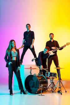 Junge kaukasische musiker, band, die im neonlicht auf gradientenstudio auftritt