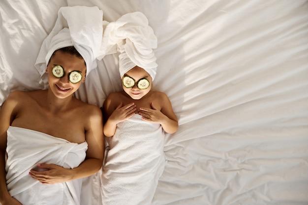 Junge kaukasische mutter und kleine tochter mit umwickeltem haar in weißen badetüchern, die auf dem bett liegen und gurkenstücke auf ihre augen auftragen. familien-spa. draufsicht