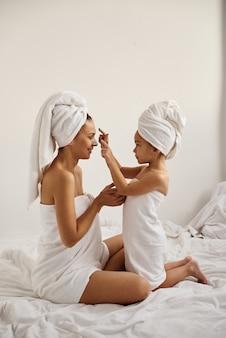 Junge kaukasische mutter und kleine tochter mit umwickeltem haar in weißen badetüchern tragen eine tonmaske auf die gesichter der mutter auf