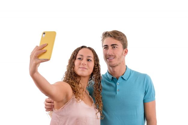 Junge kaukasische paare, die ein selfie zusammen lokalisiert auf weißem hintergrund nehmen