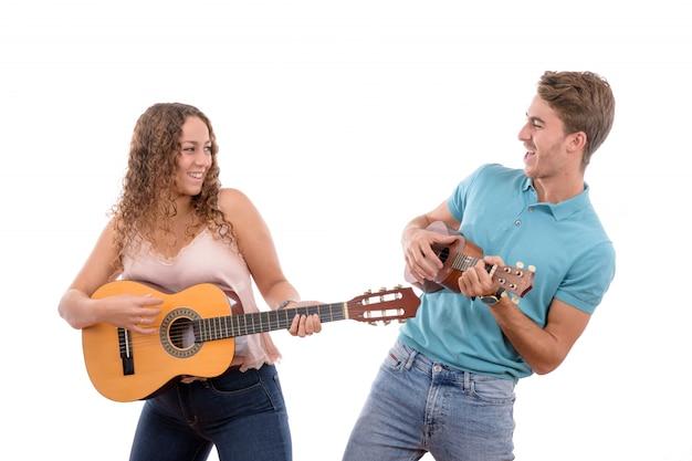 Junge kaukasische paare, die eine gitarre und eine ukulele lokalisiert auf weißem hintergrund spielen