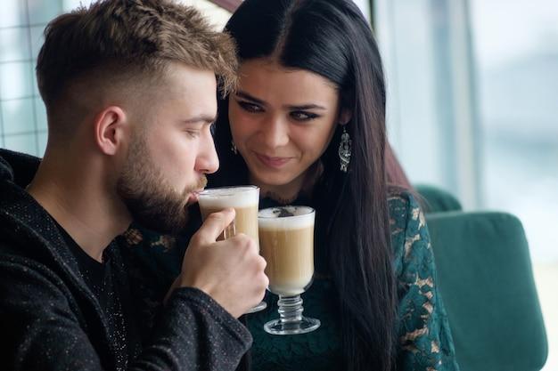 Junge kaukasische paare, die kaffee im café, mädchen betrachtet mann mit liebe in ihren augen sprechen und trinken