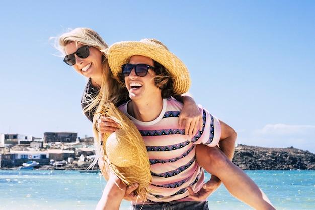 Junge kaukasische paare, die sich im sommerurlaub am strand amüsieren, touristen lieben reisen und leben zusammen