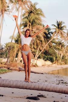 Junge kaukasische passende frau mit wassermelone am tropischen strand bei sonnenuntergang. sport suchende frau in weißem oberteil und höschen mit tropischen früchten