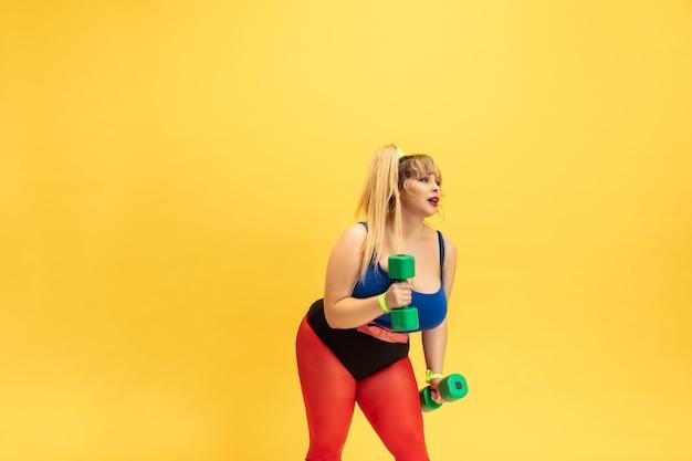 Junge kaukasische plus größe weibliche modelle, die auf gelber wand trainieren