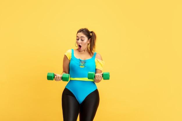 Junge kaukasische plus größe weibliches model training auf gelber wand. exemplar. konzept des sports, gesunder lebensstil, körperpositiv, mode, stil. emotionales üben der stilvollen frau mit gewichten.